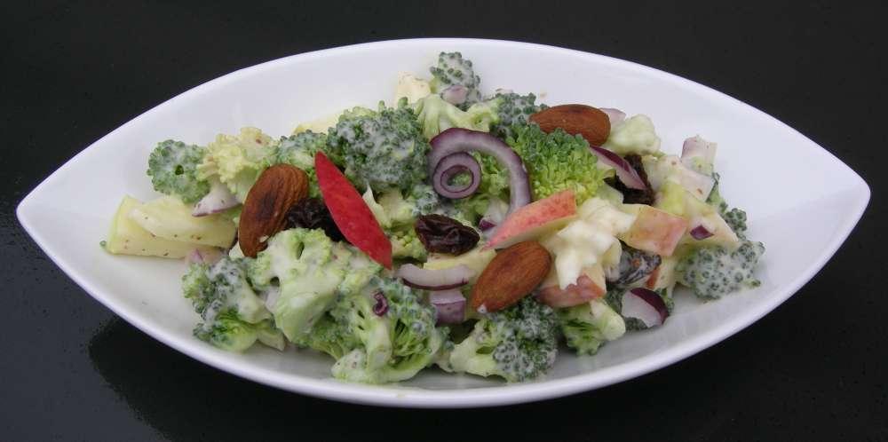 Broccolisalat med æbler, mandler og rosiner i en dejlig skyrdressing
